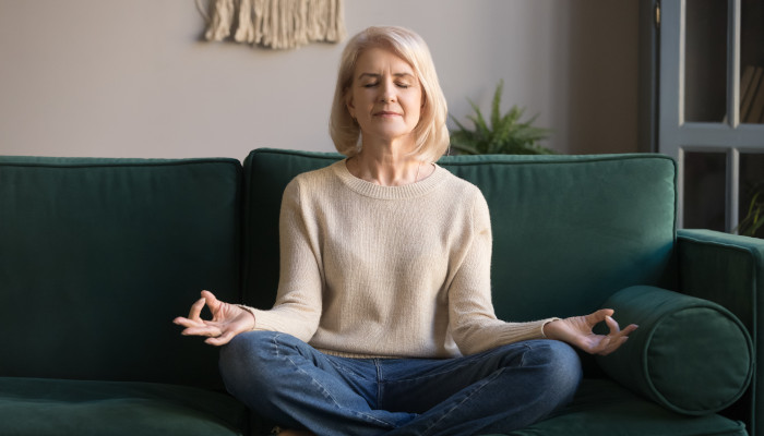 A senior caregiver meditates to manage cabin fever